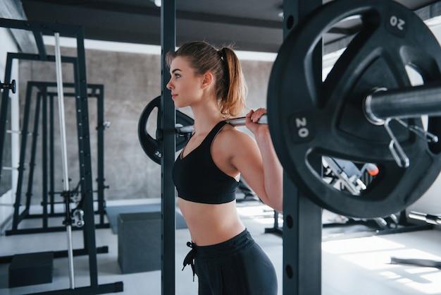 Modernes fitnessstudio. foto der herrlichen blonden frau, die übungen zu ihrer wochenendzeit tut