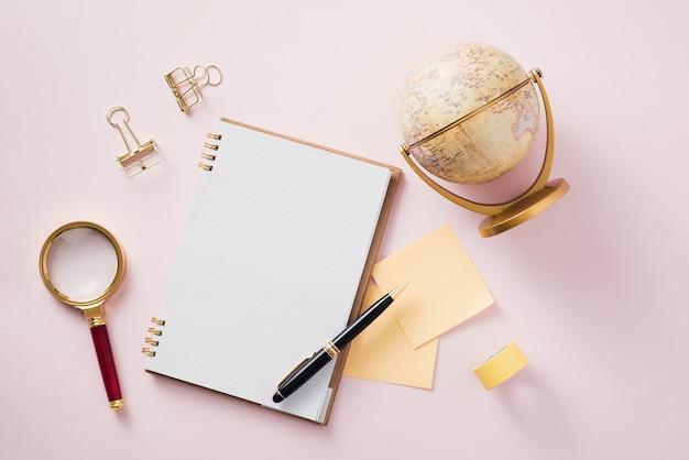 Modernes, flaches layout von notizbuch und schreibwaren auf rosa hintergrund - konzept des kreativen arbeitsbereichs