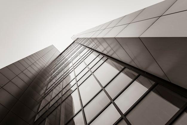 Modernes gebäude, ein fragment eines wolkenkratzers. perspektive, die in den himmel geht. sepia-tönung. architektur, design und geometrische linien