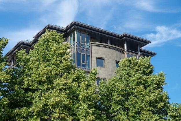 Modernes gebäude hinter grünen bäumen gegen eine blaue nahaufnahme des bewölkten himmels an einem sonnigen sommertag