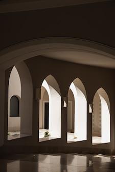 Modernes gebäude im östlichen stil mit fenstern und sonnenlichtschatten an beigefarbenen wänden
