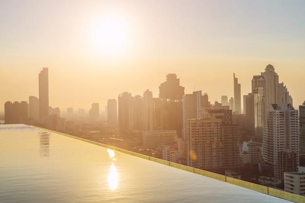 Modernes gebäude in bangkok-stadt mit swimmingpool im vordergrund bei sonnenuntergang