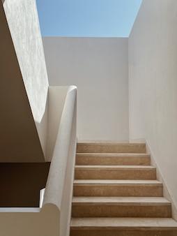 Modernes gebäude mit beigefarbenen wänden, treppen und sonnenlichtschatten