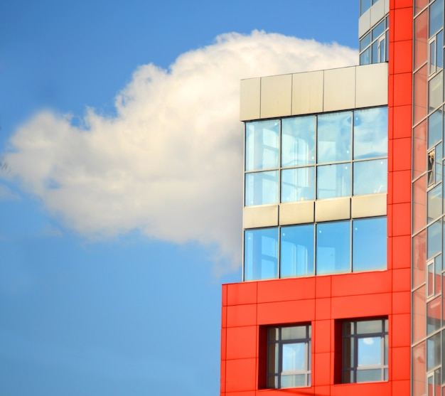 Modernes gebäude mit roten quadratischen fenstern und spiegelglas auf dem hintergrund des blauen himmels mit wolken an einem sonnigen tag