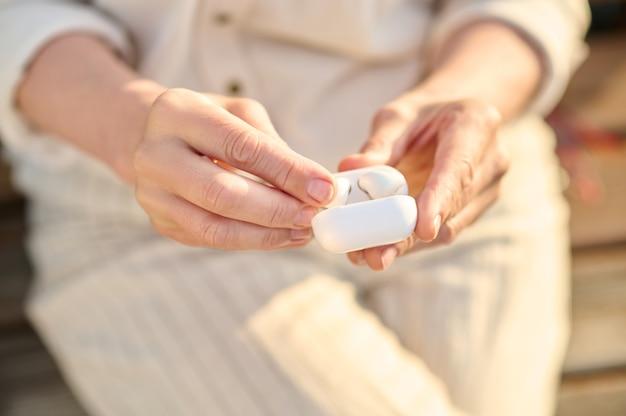 Modernes gerät. frau in leichter kleidung mit drahtlosen kopfhörern im weißen kleinen etui im freien, gesicht ist nicht sichtbar