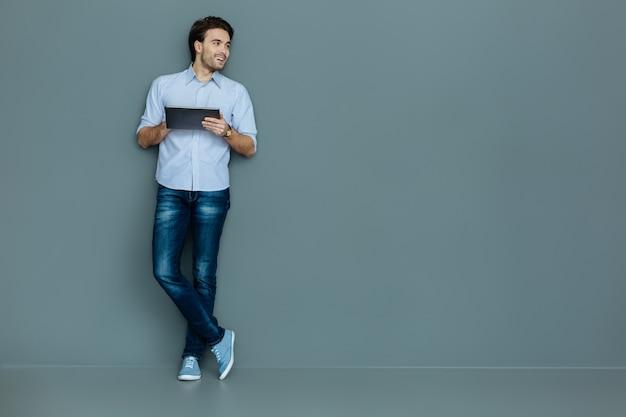 Modernes gerät. fröhlicher entzückter gutaussehender mann, der eine tafel hält und lächelt, während er sich an die wand lehnt