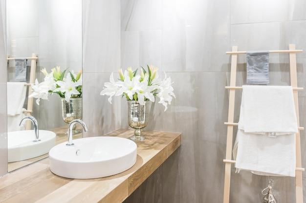 Modernes geräumiges badezimmer mit hellen fliesen mit toilette und waschbecken.