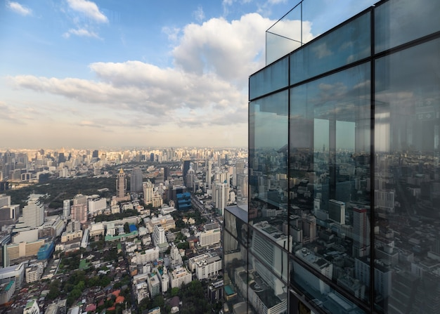 Modernes glasgebäude mit überfüllter innenstadt in bangkok city mit blauem himmel
