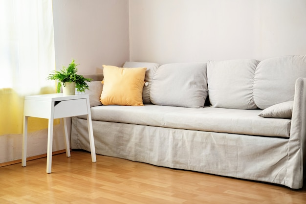 Modernes graues sofa mit gelbem kissen im wohnzimmer