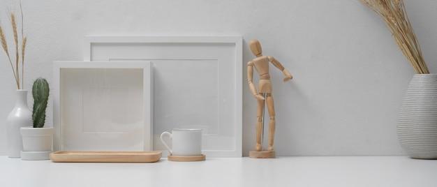 Modernes heimbüro mit modellrahmen, dekorationen und kopierraum auf weißem tisch