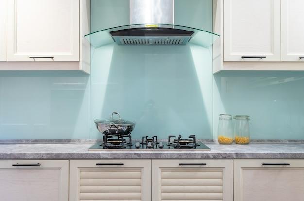 Modernes, helles, sauberes kücheninterieur mit edelstahlgeräten in einer luxuswohnung.