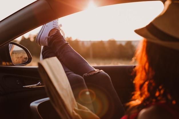 Modernes hipster-mädchen, das sich in einem auto entspannt und eine karte liest. füße vor dem fenster bei sonnenuntergang. reisekonzept