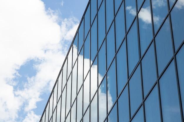 Modernes hochhausfassadengeschäftszentrum oder -wohnung mit vielen fenstern, himmel mit wolken auf einer seite. ansicht von unten, diagonale ansicht.