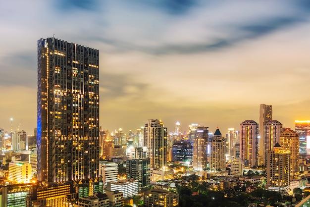 Modernes höhengebäude im geschäftsstadtzentrum von bangkok mit beweglicher wolke im himmel nachts.