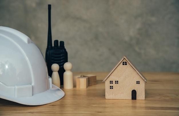 Modernes holzhaus mit kubischem block und ausrüstung auf dem tisch architekturbau von helm und walkie-talkie für die kommunikation von immobilien techniker und wartungskonzept