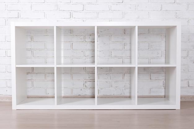 Modernes holzregal über weißem backsteinmauerhintergrund