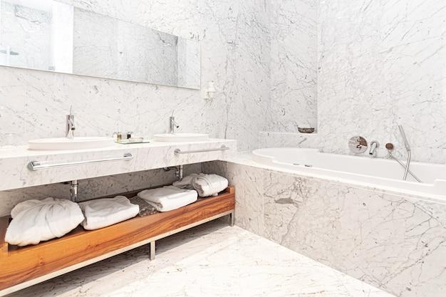 Modernes hotelbadezimmer aus weißem marmor mit badewanne und handtüchern