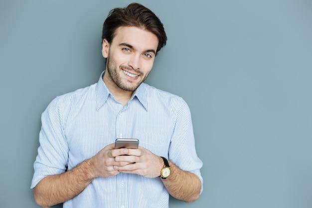 Modernes igen. glücklicher netter gutaussehender mann, der sein smartphone hält und zu ihnen lächelt, während sie eine nachricht tippen