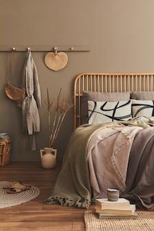 Modernes innendesign des stilvollen schlafzimmers mit dekoration, neutralem makramee, kleiderbügel, trockenblume, korb, schöner bettwäsche, decke, kissen und persönlichen accessoires