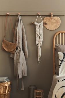 Modernes innendesign des stilvollen schlafzimmers mit dekoration, neutraler makramee, kleiderbügel, schlafrock, korb, schönen bettlaken, decke, kissen und persönlichen accessoires.