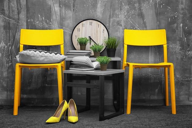 Modernes innendesign mit gelben stühlen und tischchen auf grau