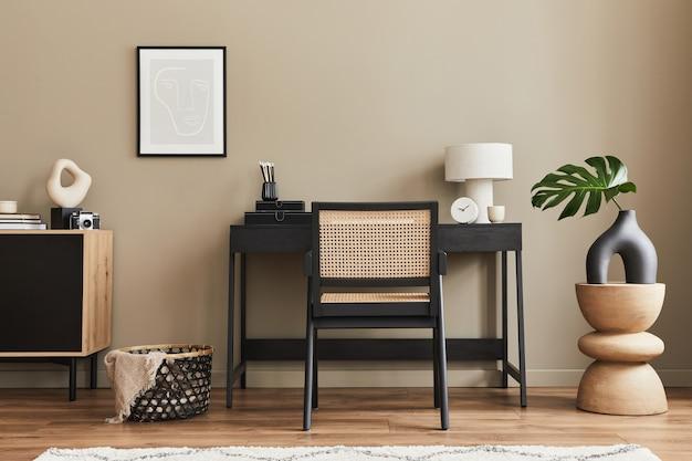 Modernes innendesign von home-office-räumen mit stilvollem stuhl, schreibtisch, kommode, schwarzem rahmen, laptop, buch, bürobedarf und eleganten accessoires in der wohnkultur.
