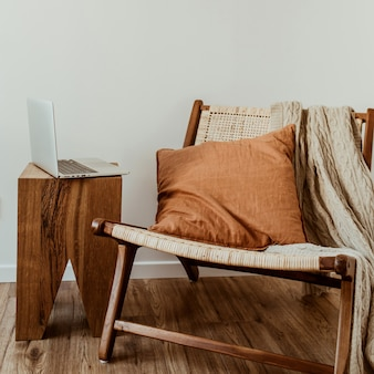 Modernes innendesignkonzept. stilvoller rattan-holzstuhl, gestricktes plaid, ingwer-kissen