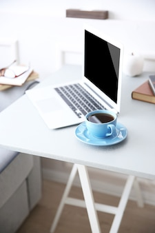 Modernes interieur. bequemer arbeitsplatz. tisch mit laptop und tasse kaffee, nahaufnahme