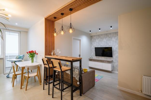 Modernes interieur der orange-weißen und blaugrünen küche mit essbereich