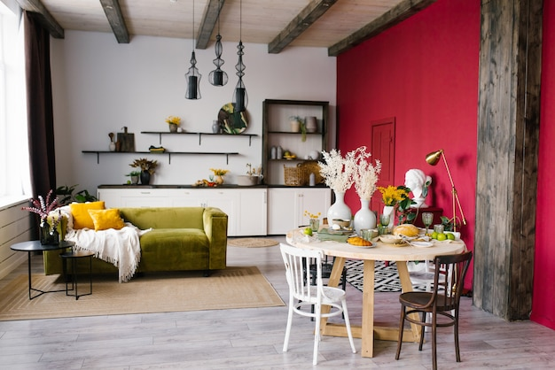 Modernes interieur des wohnzimmers mit einem grünen sofa und einem runden tisch mit verschiedenen stühlen