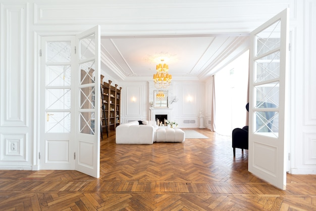 Modernes interieur einer luxuriösen großen, hellen zweizimmerwohnung. weiße wände, luxuriöse teure möbel, parkett und weiße innentüren