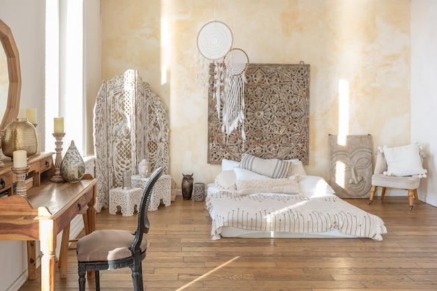 Modernes interieur eines hellen zimmers in einer zweistöckigen wohnung mit dekorationsgegenständen im bali-stil mit balkon. weiße wände, holzböden und vintage-möbel