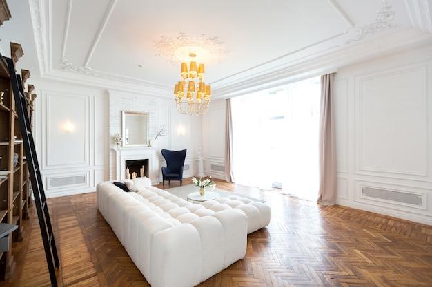Modernes interieur eines luxuriösen großen hellen wohnzimmers. weißes teures sofa und holzregale, weiße wände mit leisten und ein luxuriöser kronleuchter