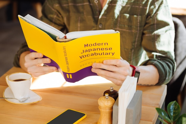 Modernes japanisches vokabular. nahaufnahme eines buches über die japanische sprache, das von einem netten jungen mann gelesen wird