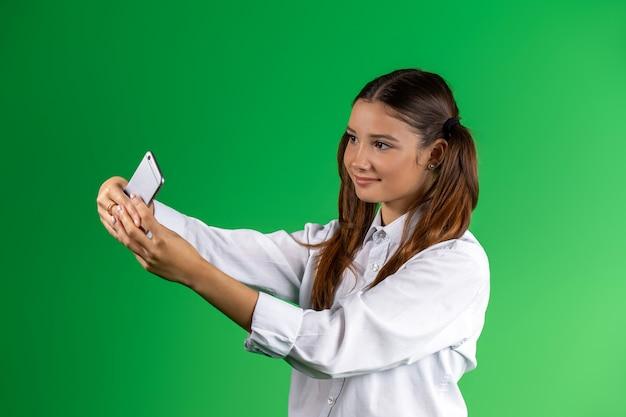 Modernes junges mädchen in der schulkleidung, das ein selfie auf einem mobiltelefon nimmt