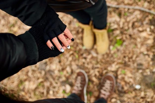 Modernes junges paar händchen haltend im wald outdoor-reisekonzept, draufsicht, liebe für immer, valentinstag.
