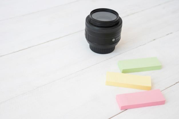 Modernes kameraobjektiv mit bunten klebrigen anmerkungen über hölzernen schreibtisch