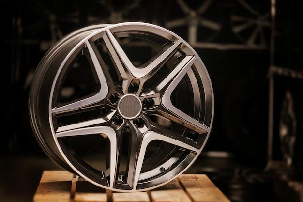Modernes kfz-leichtmetallrad aus aluminium auf schwarzem hintergrund, industrie. auf einem strukturierten holztisch.