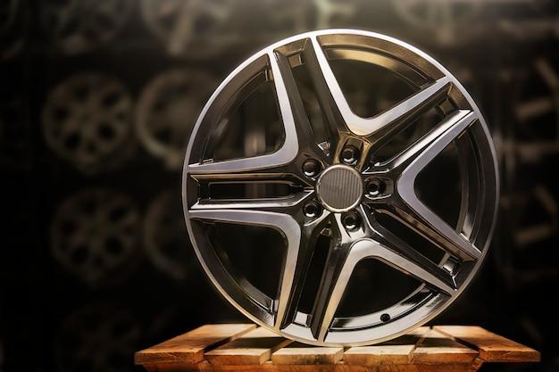 Modernes kfz-leichtmetallrad aus aluminium auf schwarzem hintergrund, industrie.