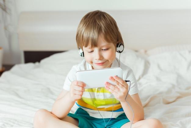 Modernes kleines kind, das auf bett mit smartphone in seinen händen sitzt