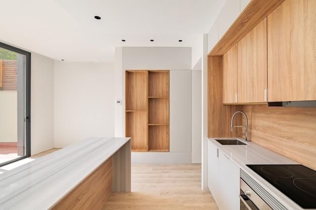 Modernes kücheninterieur mit insel und holzmöbeln leerer innenraum der hellen renovierten wohnung