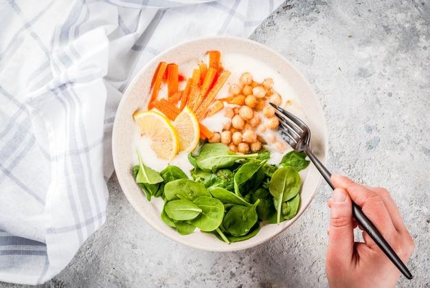 Modernes lebensmittel des strengen vegetariers, person essen wohlschmeckende joghurtschüssel mit bohnen