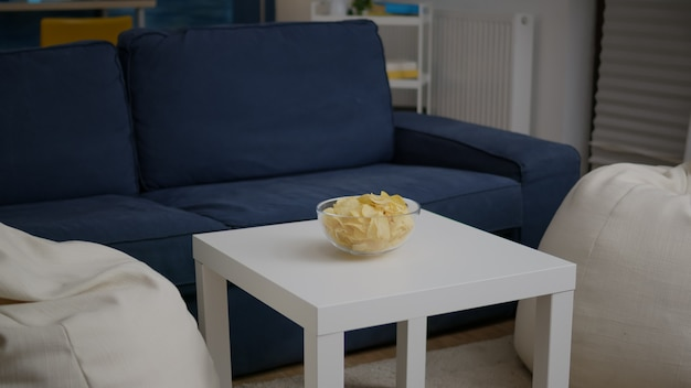 Modernes, leeres apartment mit niemandem darin ist bereit für eine nachtparty mit pommesschüssel auf einem holztisch. das wohnzimmer ist für freunde vorbereitet, die spät in der nacht eine geburtstagsparty am wochenende feiern