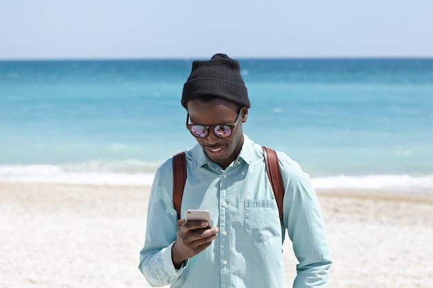 Modernes lifestyle-, technologie- und kommunikationskonzept. attraktiver junger schwarzer europäischer hipster in hemd, hut und sonnenbrille, der das schnelle 3g- oder 4g-internet genießt, während er das wochenende am meer verbringt