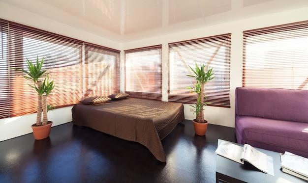 Modernes loft-schlafzimmer mit viel tageslicht doppelbett und bequemem sofa mit couchtisch