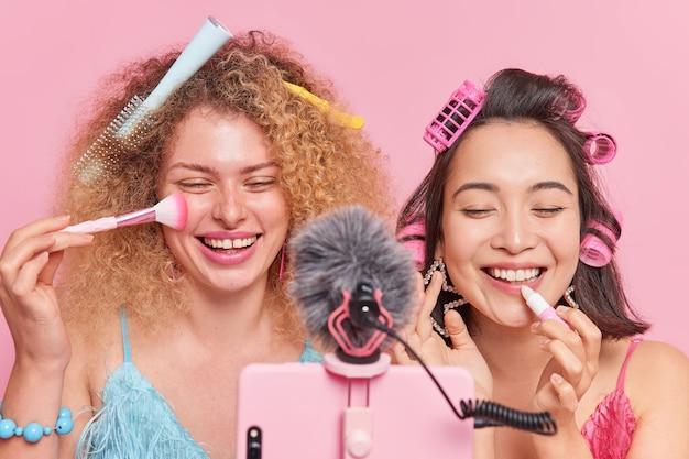 Modernes marketing. fröhliche diverse frauen nehmen inhalte für lifestyle-blog auf puder und lippenstift auftragen lachen fröhlich geben tipps, wie man schön bleibt, nebeneinander vor der handykamera stehen