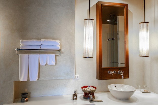 Modernes marmorwaschbecken in einer toilette oder einem hotelbadezimmer mit toilettenartikeln und frischen, sauberen handtüchern