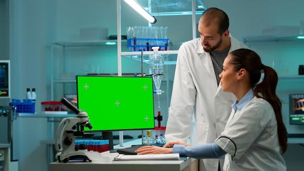Modernes medizinisches forschungslabor mit zwei wissenschaftlern, die computer mit grünem chroma-key-bildschirm verwenden. ärztespezialisten diskutieren innovative behandlung, fortschrittliches wissenschaftliches labor für medizin.