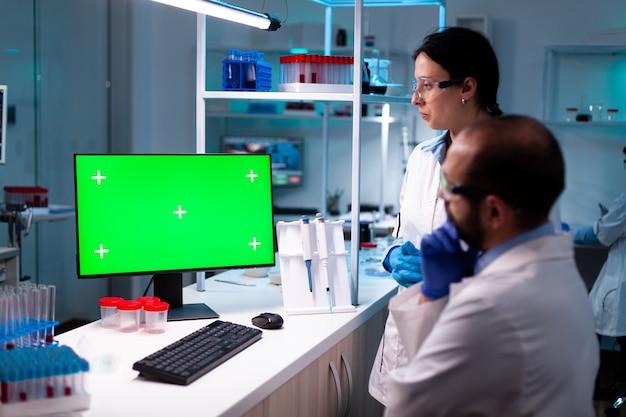 Modernes medizinisches forschungslabor mit zwei wissenschaftlern, die computer mit grünem chroma-key-bildschirm verwenden