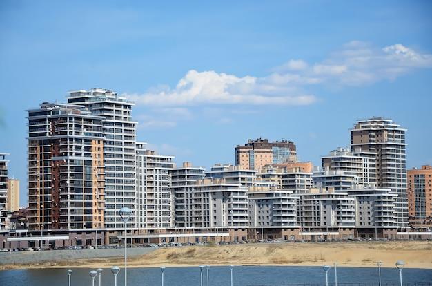 Modernes mehrstöckiges gebäude in der stadt am ufer auf blauer himmelsoberfläche